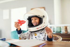 Child playing with astronaut helmet and rocket